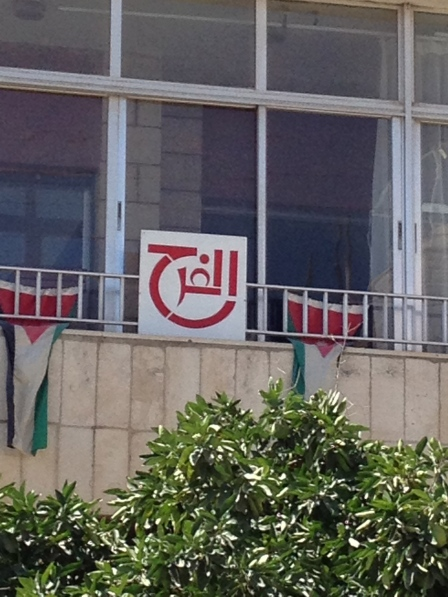 "One of several identical signs on a building in my neighborhood. It reads, ""al-farah,"" which means ""joy"" in English."