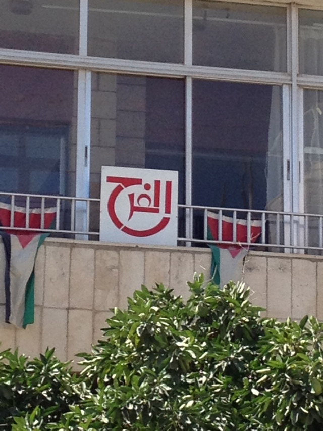 """One of several identical signs on a building in my neighborhood. It reads, """"al-farah,"""" which means """"joy"""" in English."""