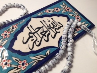 """Islamic prayer beads and a tile painted by Armenian Christians in Jerusalem. It displays the Islamic invocation """"In the name of God, the Most Compassionate, the Most Merciful."""""""
