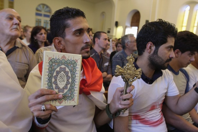 Iraqi man holds up cross and Qur'an at interfaith solidarity event. Source: Buzzfeed