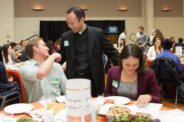 Adam Park, chaplain of George Washington the Newman Center, greets students at the university's Interfaith Journeys Dinner.